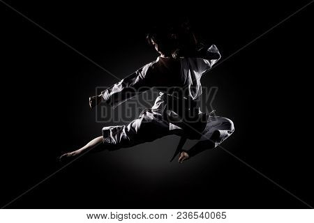 Girl Exercising Karate, Kick In The Air Against Black Background
