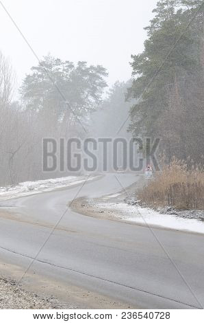 Crossroads On A Suburban Asphalt Road In Wintertime During A Blizzard