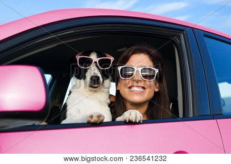 Woman And Dog In Pink Car On Summer Road Trip Vacation. Funny Dog With Sunglasses Traveling. Travel