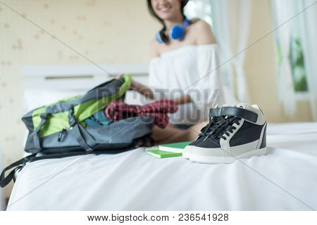 Cheerful Female Packing Suitcase And Getting Ready For Traveling.bedroom Full Of Things Ready To Be