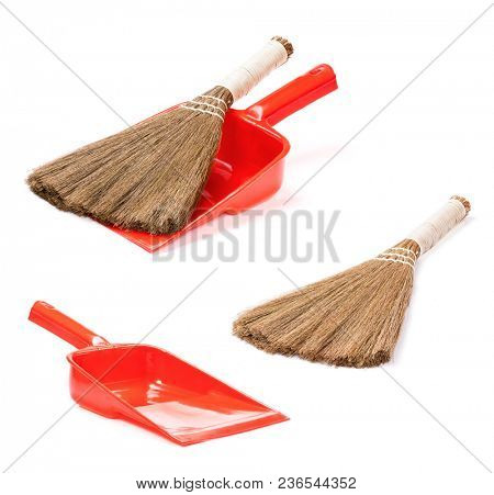 Set of plastic red dustpan with new broom, isolated on white background
