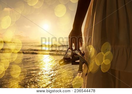 Summer Lifestyle Of Pretty Woman Holding Sandals And Relax On Beach. Positive Emotions. Summer Conce