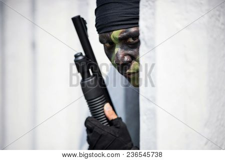Special Forces Soldier Or Private Military Holding Gun Behind Concrete Obstacle.