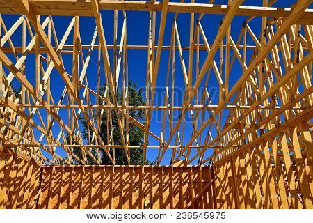 Pre-built Rafters On A Building Project Cast Their Shadows On The Walls