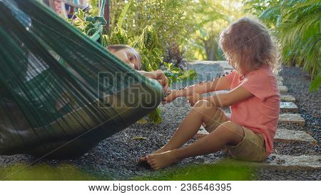 Young Mother Lying In Hammock And Playing With Her Little Daughter With Stones At Green Beautyful Ga