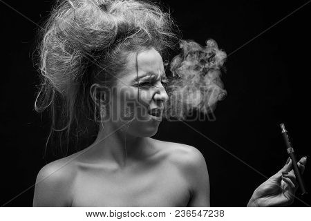 Young Woman Smoking Electronic Cigarette On Black Background, Monochrome, Grimacing, Cough