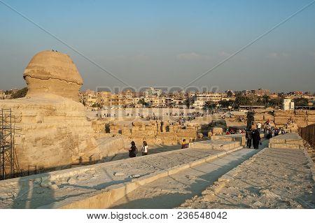 Giza, Egypt - November 11, 2006: Tourists Visiting Sphinx Over Cairo Background