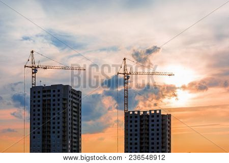 Silhouette Of Tower Cranes And Unfinished Multi-storey High Buildings Under Construction Site In The