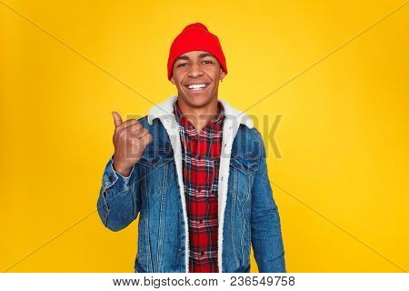 Stylish Ethnic Man In Red Hat And Jacket Smiling Contently At Camera Pointing Away With Big Finger.