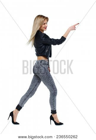 Side view of a girl walking with a pointing hand. going girl showing.  backside view of person.  Rear view people collection. Isolated over white background. Blonde on heels goes to goal