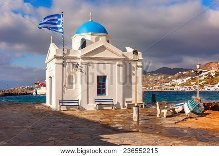 Agios Nikolaos Christian Church, Typical Greek Church Building And Large Waving Greek Flag In Old Po