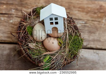 Miniature White Toy Model House Rests In Nest With Eggs On Rustic Old Vintage Wooden Background. Eco