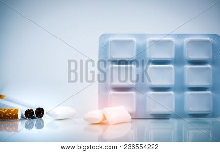 Nicotine Chewing Gum In Blister Pack Near Pile Of Cigarette. Quit Smoking By Use Nicotine Gum For Re