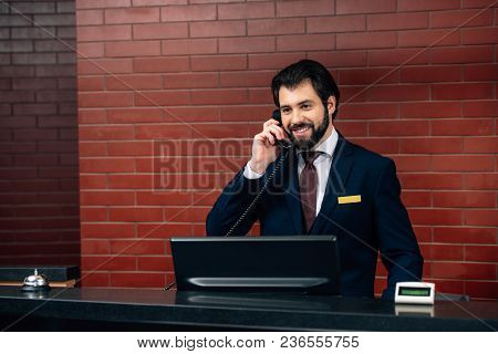 Smiling Hotel Receptionist Taking Phone Call At Workplace