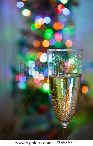 Wine Glass With Champagne Is On A Background Of Multicolored Lights