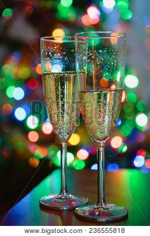 Two Wine Glasses With Champagne Are On A Background Of Multicolored Lights