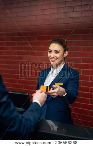 Young Happy Hotel Receptionist Taking Credit Card From Customer