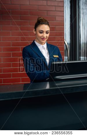 Young Attractive Hotel Receptionist Using Computer At Workplace