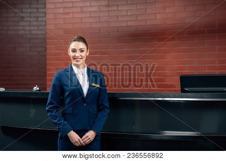Young Beautiful Hotel Receptionist Standing In Front Of Workplace