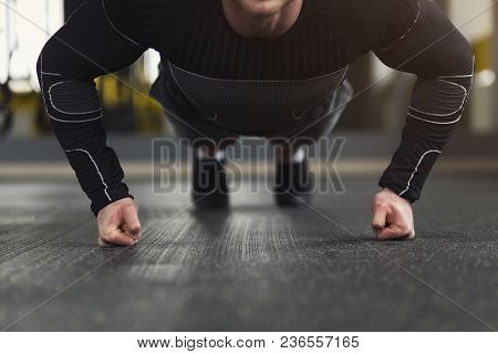 Young Man Workout In Fitness Club. Unrecognizable Guy Making Plank Or Push Ups Exercise On Fists, Tr