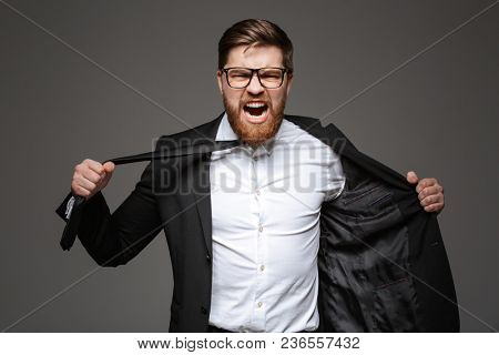 Portrait of a mad young businessman dressed in suit trying to undress isolated over gray background