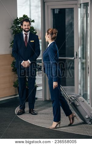 Businesswoman Going Out Of Hotel Luggage And Looking At Doorman