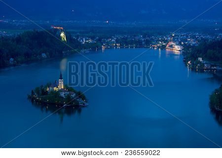 Scenic View Of Lake Bled From Above At Night With Backlit Island Church, Castle And Buildings Along