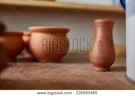 Ceramic Dishware On Worktop And Shelves In Pottery Workshop, Selective Focus, Close-up, Shallow Dept