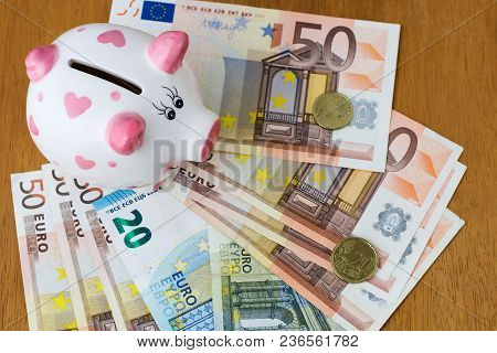 Piggy Bank And Euro Banknotes On A Wooden Table. Finance. Saving. Business.