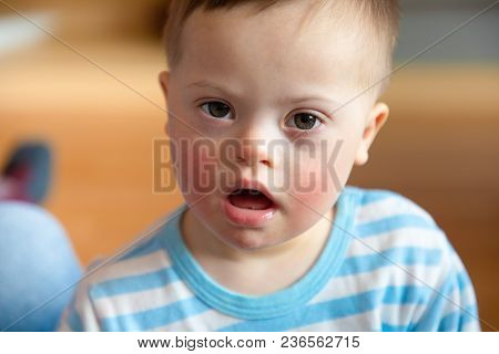 Portrait Of Cute Baby Boy With Down Syndrome In Home Living Room