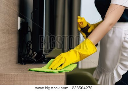 Cropped Shot Of Maid In Uniform Wiping Shelf With Rag And Aerosol Furniture Cleaner