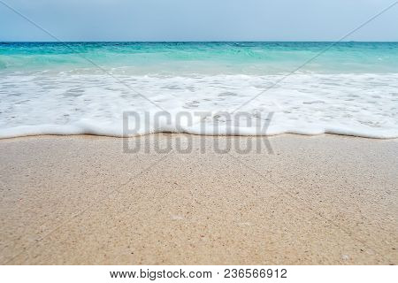 Soft Blue Ocean Wave On Sandy Beach. Background. White Sand On The Beach With Turquoise Water. An Ex