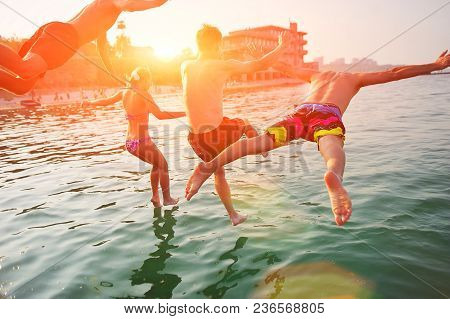 Group Of Happy People Having Fun Jumping In The Sea Water From A Pier. Friends In Mid Air On A Sunny