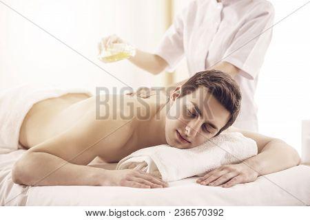 Masseur Doing Massage On Man Body With Spa Oil In Beauty Salon.