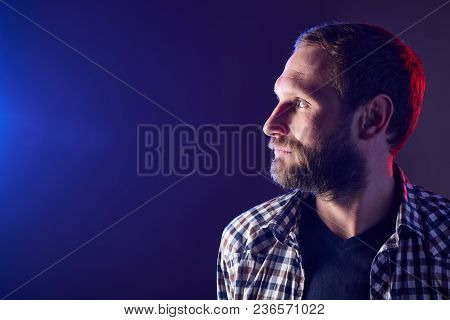 Profile Closeup Portrait Of Bearded Man Looking To The Side Over Dark Background, Red And Blue Backl