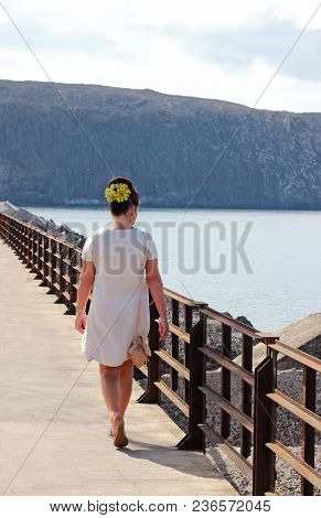 Sixties Retro Style: Rear View Of A Woman With A Beehive Hairdo, Devorated With Artifical Flowers, W