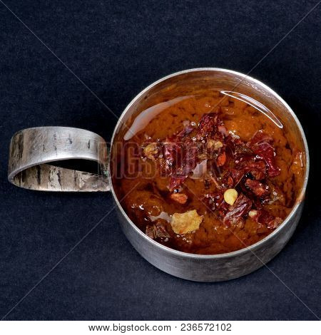 Hot Homemade Red Chili Sauce In Vintage Tin Gravy Boat Closeup On Black Background