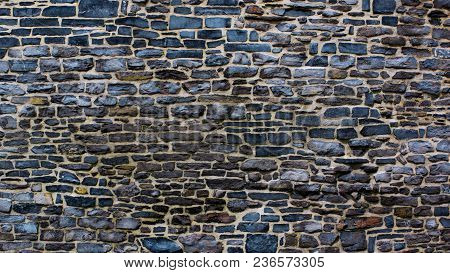Old Cracked And Grinded Down Grey And Brown Bricks Wall With Concrete As Background