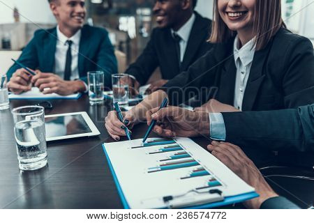 Colleagues In Business Suits Study Charts Depicted In Negotiation Room. Business Meeting. Encounter