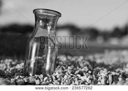 Cracked Glass Bottle Sitting In Gravel At A Cemetery In Black And White.