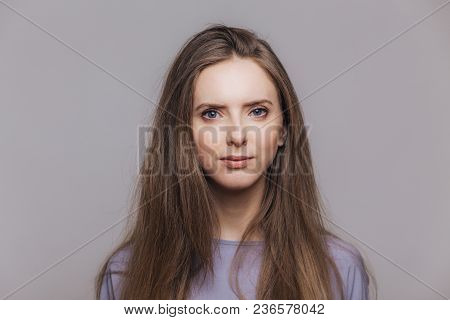 Portrait Of Serious Brunette Female With Healthy Skin, Looks Confidently At Camera, Has Dark Straigh
