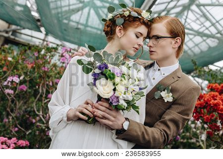 Low Angle View Of Beautiful Young Redhead Wedding Couple Embracing In Botanical Garden