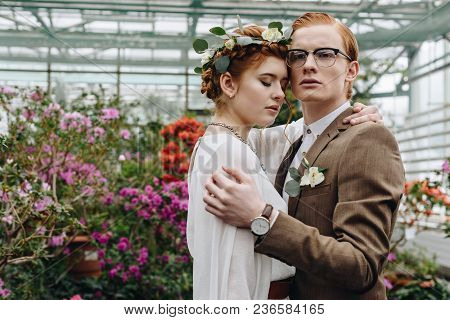 Tender Young Red-haired Wedding Couple Embracing While Standing Between Flowers In Botanical Garden