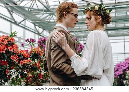 Beautiful Young Red-haired Wedding Couple Embracing And Looking At Each Other While Standing Between