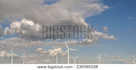Windmills In A Sunny Afternoon Sky Producing Energy And A Pale Filter.