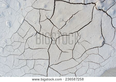 Grey Color Dry  Cracked Muddy  Earth As A Background Texture