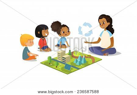 Female Teacher Discusses Ecology Green-city Using Model Landscape, Children Sit On Floor In Circle A