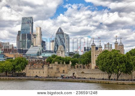 The City of London financial district, The Tower of London, Traitors Gate and the river Thames. Unidentifiable people walk along the river bank in summer