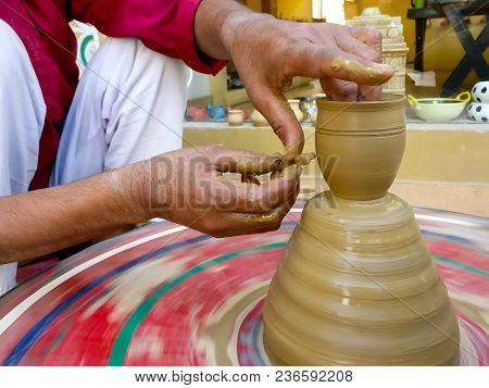 Potter Making Clay Pots On A Colorful Pottery Wheel. This Ancient Handicraft Has Been Passed Down Fr