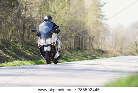 A Man Enjoys While Riding A Motorcycle Scooter On Forest Roads